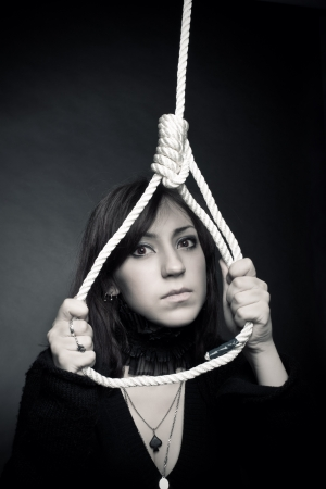 Sad girl with gallows over dark background Stock Photo - 17787984