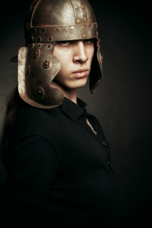 Brave young man in roman helmet posing over dark background photo