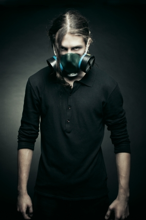 Brutal post apocalyptic man in respirator posing over dark background photo