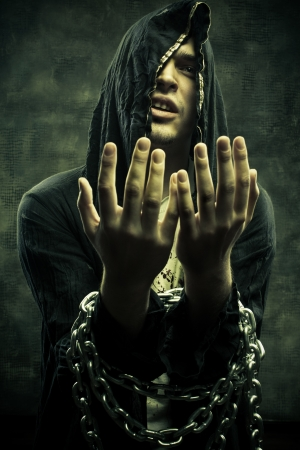 Portrait of miserable fanatical young man in hood bounded by chains.