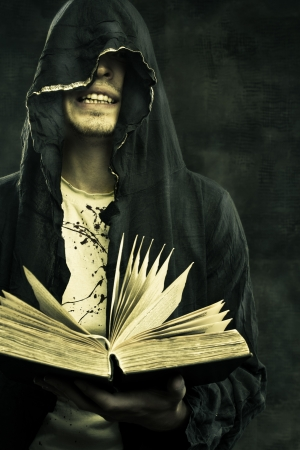 Portrait of sinister prophet in hood holding book