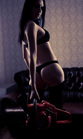 Seductive girl in underwear posing with chainsaw photo
