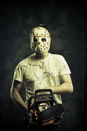 Scary mad maniac in mask with bloody chainsaw photo