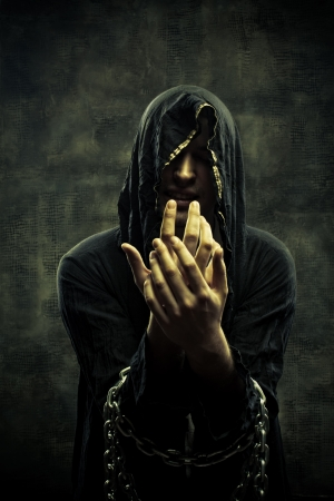portent: Portrait of miserable chained young man in hood Stock Photo