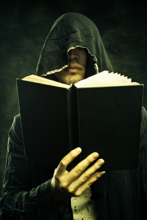 Portrait of sinister cultist in hood with book  Stock Photo