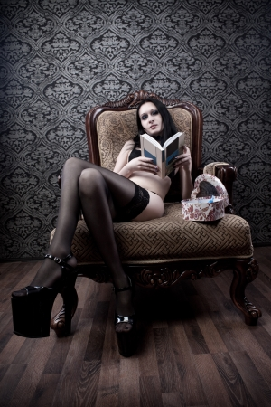 Seductive dark-haired girl sitting in armchair with book photo
