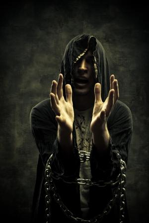soothsayer: Miserable profeta con las manos en las cadenas posando sobre fondo oscuro Foto de archivo