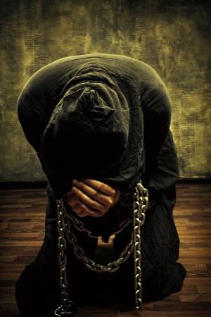 Miserable monk praying on his knees in dark room 스톡 콘텐츠