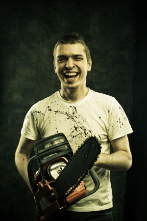 Mad sinister maniac with  bloody chainsaw  photo
