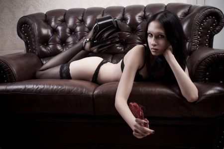 Sexy girl in black underwear laying on a sofa with heart photo