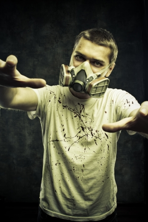 Man in gas mask posing over grunge background photo