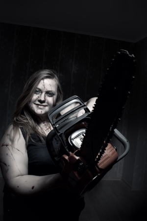 Mad bloody girl with chainsaw posing in empty dark room photo