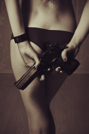 Young elegant lady in underwear holding gun