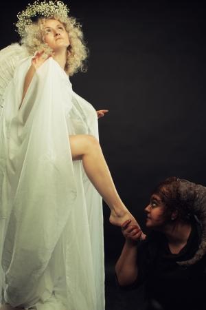 enslave: Demon holds angel leg over dark background.