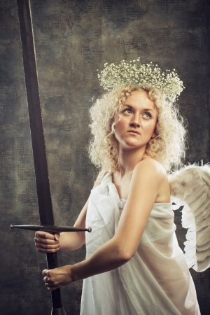 Little angel with large sword over grange background photo