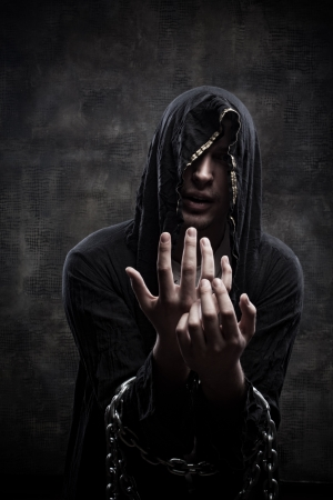 predictor: Portrait of miserable chained young man in hood Stock Photo