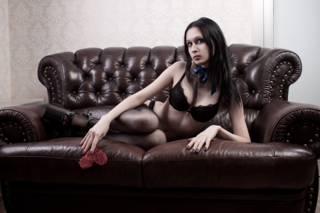 Seductive girl in underwear laying on a sofa photo