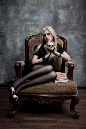 Gothic girl with skull sits on the armchair 스톡 콘텐츠