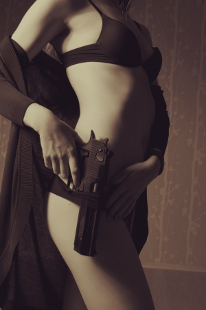 Young elegant lady in underwear holding gun photo