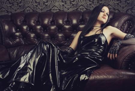 Gothic girl in dark dress lays on divan