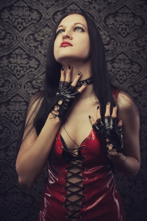 Gothic girl in red latex dress over vintage background photo