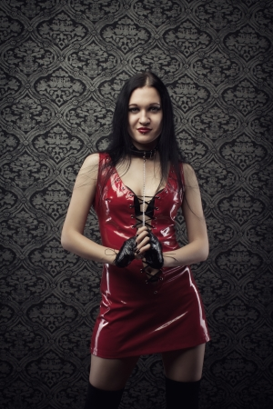 Attractive girl in red latex dress over vintage background photo