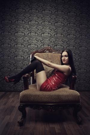 mistress: Seducente ragazza in abito rosso in lattice si siede in poltrona