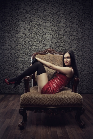 Seductive girl in red latex dress sits in armchair photo