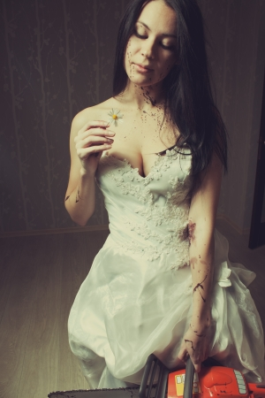 Pretty bride with chamomile and chainsaw stands in empty room photo