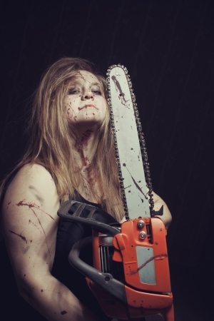 Bloody maniac woman with chainsaw stands in empty dark room photo
