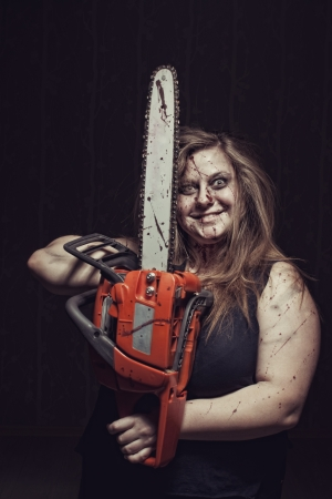 Bloody maniac  with chainsaw stands in empty dark room 스톡 콘텐츠