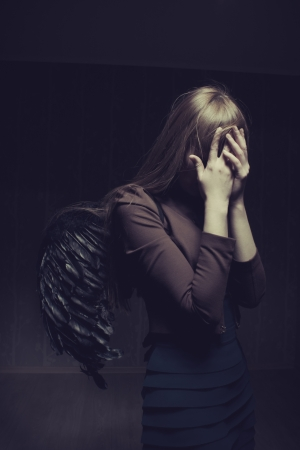 miserable: Miserable girl with artificial wings standing in a dark empty room Stock Photo
