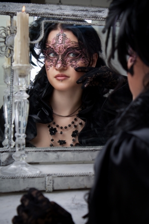 Beautiful gothic lady in mask at mirror photo
