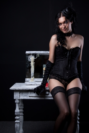Seductive young woman in black corset and panties sits on the white table Stock Photo - 19857541