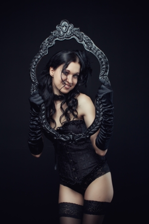Attractive gothic girl in black corset and panties with frame over dark background Stock Photo - 19857540