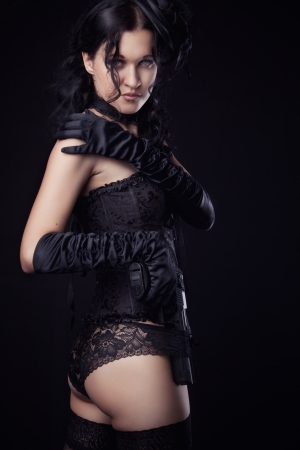 Sexy gothic lady with gun over dark background photo