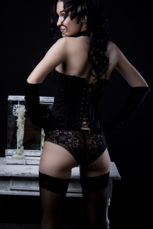 Seductive old-fashioned girl posing over dark background  Rear view   Stock Photo - 19803382