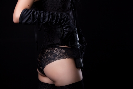 Young  lady in underwear with gun over black background