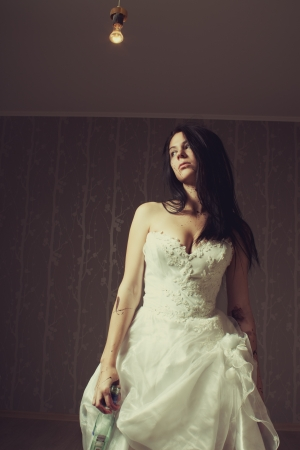 debauch: Miserable bloody bride with bottle of alcohol stands  in empty dark room