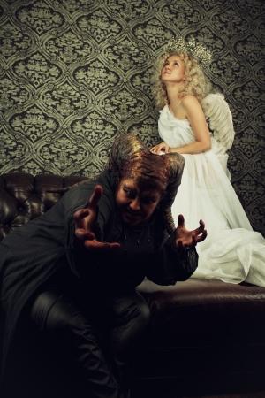 angry angel: Aggressive demon and innocent angel on a sofa