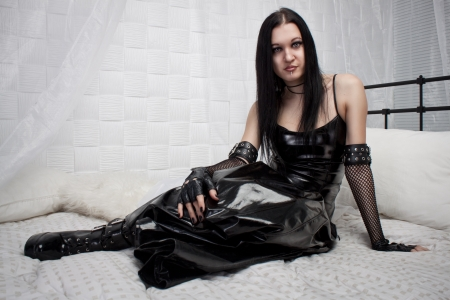 Beautiful gothic lady in latex  sits on the bed photo