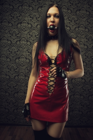 Pretty girl in red latex dress with mouth gag stands in an empty room  Stock Photo