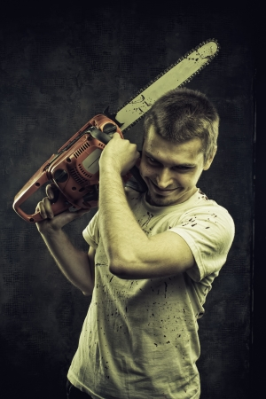 Mad maniac with bloody chainsaw over grunge background photo