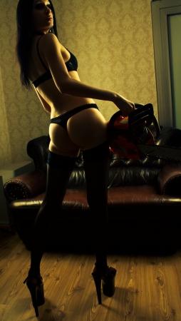 Seductive girl in underwear holding bloody chainsaw photo