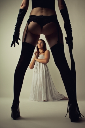 Beautiful cute model in white dress stands on knees next to legs of her dominatrix with lash