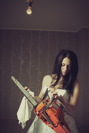 Pretty bride cleaning her bloody chainsaw photo