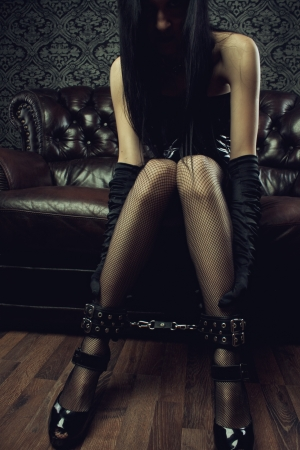 Sexy gothic girl with legs in leg cuffs photo