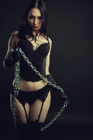 Seductive girl in black lingerie with chains over dark background