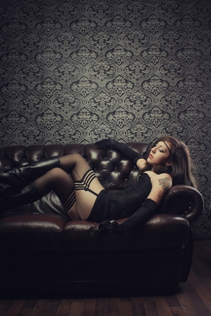 Seductive old-fashioned girl laying on a sofa photo