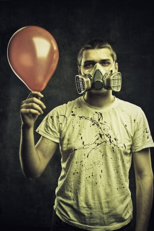 Man in respirator with balloon in his hand over grunge background photo